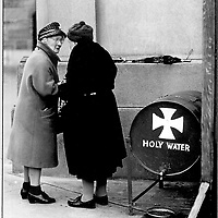 Two old ladies chat while collecting holy water from a barrel behind a cathedral in Dublin, Ireland.