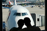 Honeymooners cuddle in front of a British Airways 747 before their round-the-world adventure from Heathrow Airport's T5
