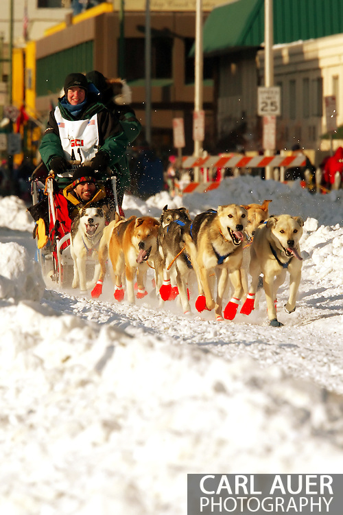 3/3/2007:  Anchorage Alaska -  With a team of dogs wearing bright orange booties to protect their paws from rocks and ice, the team of Rookie Ellen Halverson of Wasilla, AK races down the street during the Ceremonial Start of the 35th Iditarod Sled Dog Race