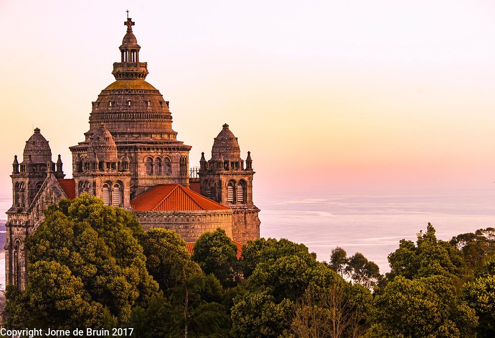 The fairytale like Sanctuary of Santa Luzia overlooking the ocean at sunset.