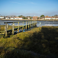 View across the estruary in Bosham looking towards old cottages with old wooden jetty