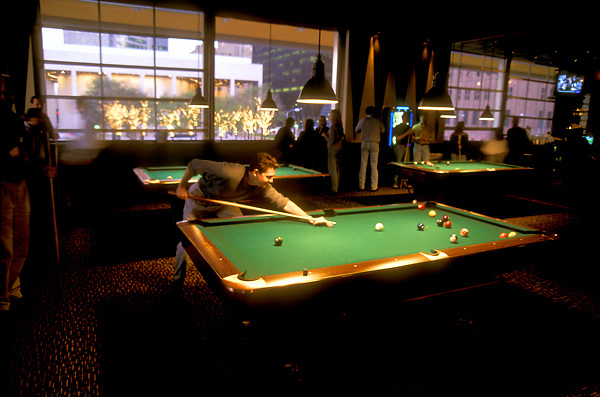 Stock photo of a man shooting billiards at a pool hall