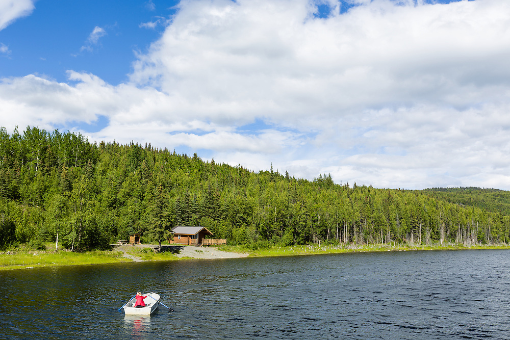 A woman rows a skiff to the US Fish and Wildlife Service cabin at Upper Ohmer Lake in the Kenai National Wildlife Refuge on the Kenai Peninsula in Southcental Alaska. Summer. Afternoon. Model Released.