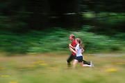 Young adult couple jogging on Pre's Trail, Alton Baker Park, Eugene, Oregon.