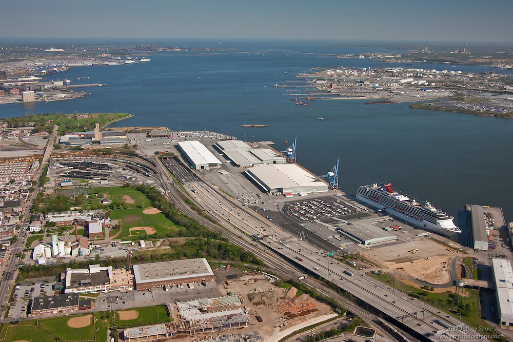 Maryland Cruise Passenger Terminal and South Locust Point at the Port of Baltimore with the cruise ship Carnival Pride sailing  with Key Bridge and the Patapsco River