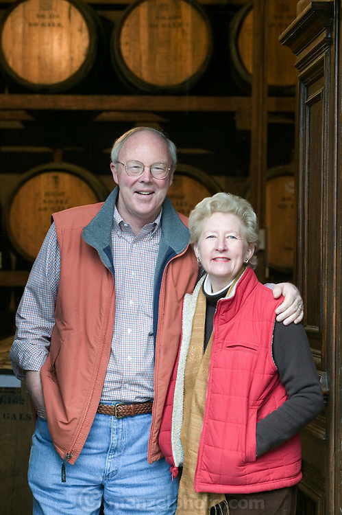 Stony Hill Winery, St. Helena, CA (Napa Valley). Peter and Willinda McCrea, owners, in the winery with doors carved by Peter's father who started the winery. Stony Hill Winery is known for producing fine white wines which are aged in oak barrels that have been used for as many as 30 years, thereby not adding much oak flavor at all to the wine..