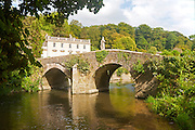 Bridge crossing the River Frome and the classical Georgian facade of Iford Manor, near Freshford, Wiltshire, England, UK