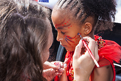 London, August 24th 2014. Final touches to makeup are applied as revellers prepare to participate in 2014's Notting Hill Carnival in London, celebratingWest Indian and other cultures, and attracting hundreds of thousands to Europe's biggest street party.