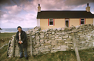 Crofter Alistair Macleod standing outside his house at Midfield, Melness on the Kyle of Tongue on Scotland's north coast. Crofting was a traditional way of life for many people in the Highlands and Islands of Scotland. It was a system of small-scale agriculture where the individual farmers grew small amounts of crops and kept sheep, cattle and other livestock in small-holdings.