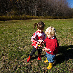 A young brother and sister look at a caterpillar in a field.  The Common Pasture in Newburyport, MA. MR