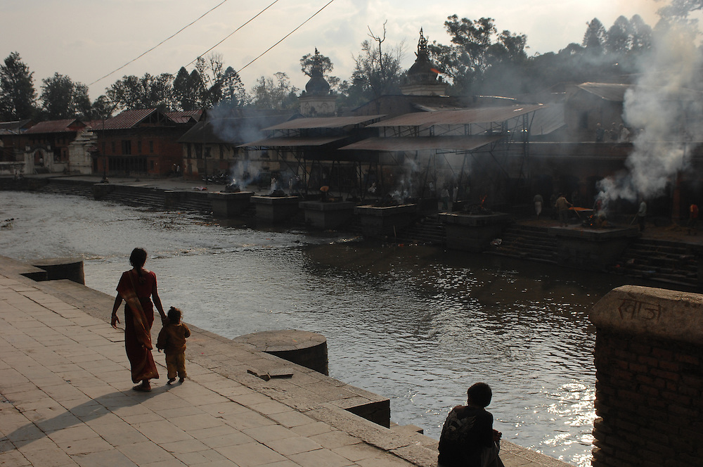 A mother and child look over at the cremations across the Bagmati river at Pashupatinath Temple, in Kathmandu, Nepal.