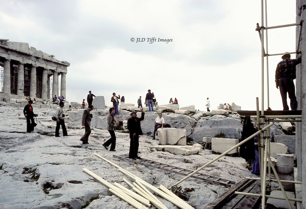 Acropolis, Propylaea, workmen doing repairs with scaffolding and tools.  One on the ground gestures to another on scaffolding by the Propylon.  Tourists wander about, some picking their way toward the Propylon.  Parthenon itself partially visible on the left.