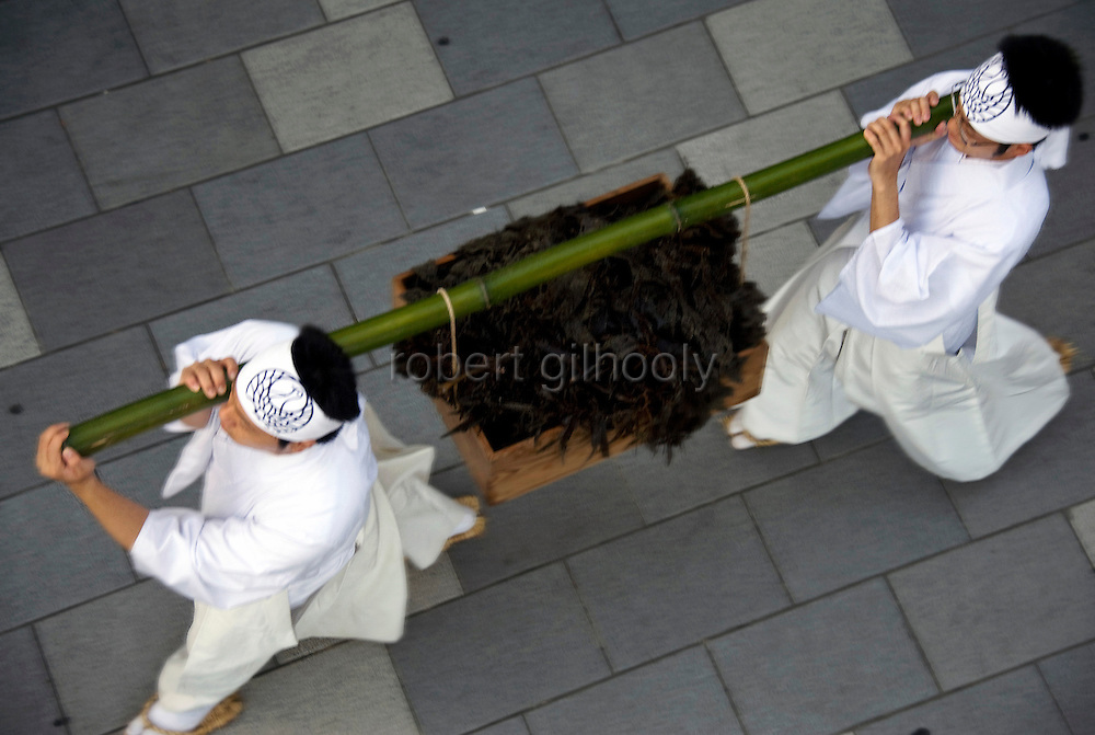 A box filled with seaweed past a torii gate in the middle of the main street by priests during a purification ritual known as hamaorisai at the start of the 3-day Reitaisai festival in Kamakura, Japan on  14 Sept. 2012.  As a symbol of the purification, priests collect the seaweed from the sea and take it back to the shrine, hanging pieces around the shrine grounds to appease the gods. Photographer: Robert Gilhooly