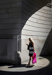 © Licensed to London News Pictures. 25/06/2018. London, UK. A city worker holds a pink carrier bag as she passes through a circle of sunlight formed at the corner of the Bank of England as high temperatures remain in most of the UK. Photo credit: Peter Macdiarmid/LNP