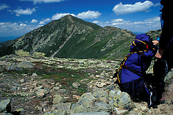 A hiker gets ready to hike to Mt. Lincoln  in the distance.   Alpine zone.  Little Haystack Mtn, White Mtns, NH