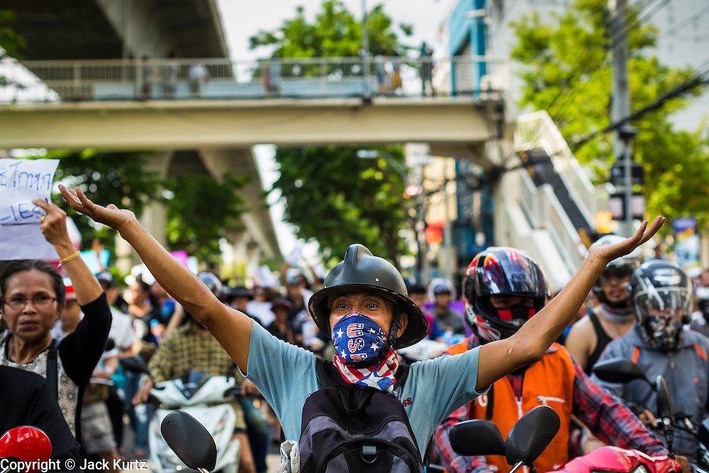 24 MAY 2014 - BANGKOK, THAILAND:  A Thai anti-coup / pro-democracy protestor leads marchers up Phahon Yothin Street towards Democracy Monument in Bangkok. There were several marches in different parts of Bangkok to protest the coup that unseated the popularly elected government. Soldiers and police confronted protestors and made several arrests but most of the protests were peaceful. The military junta also announced that firing of several police commanders and dissolution of the Thai Senate. The junta also changed its name from National Peace and Order Maintaining Council (NPOMC) to the National Council for Peace and Order (NCPO).   PHOTO BY JACK KURTZ