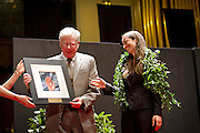 Rabbi Melissa Weintraub smiles as she recieves her prize, a work of art crafted by Curator of Academic and Public Outreach for Faulconer Gallery, Tilly Woodward. President Emeritus of Grinnell College George Drake, left, presents the award.