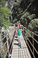 Family with children (7-12) in mountains crossing bridge