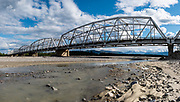 "The Black Veterans Memorial Bridge carries the Alaska Highway across the Gerstle River, 29 miles east of Delta Junction, in Alaska, USA. Free camping is available at Gerstle River Wayside just west of the bridge. Originally built in 1944, it is one of four ""steel through truss-style"" bridges on the Highway. It was renamed the Black Veterans Memorial Bridge in 1993 as a tribute to 3695 soldiers of the Army and the Corps of Engineers for their contribution in building the Alaska Highway. This image was stitched from multiple overlapping photos."