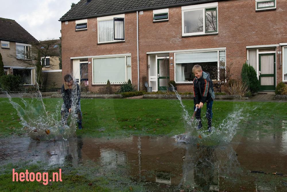 twee jongens spelen in het multatuliplantsoen te hengelo (o)met overtollig regenwater door er met scheppen op te slaan. dit geeft een hard knallend geluid