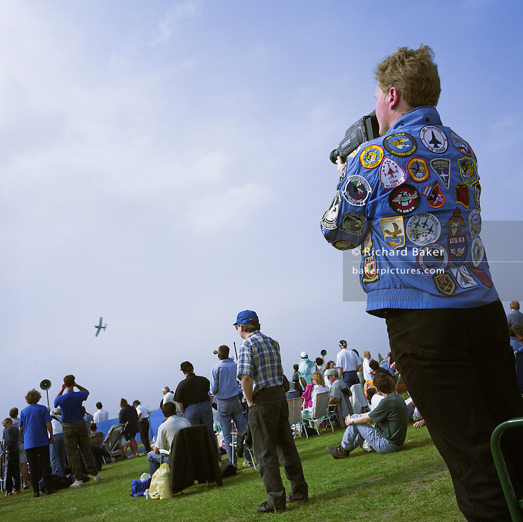 Spectators watch an air show at North Weald in Cambridgeshire, England. A man films a lone aircraft that banks across the summer sky. The enthusiast's blue denim jacket is almost fully-covered with aeronautical badges which depict various foreign military aerobatic teams, including the Swiss, Norwegian and German squadrons, whose emblems have been stitched into the fabric. Plane spotters form hardcore groups of aviation pilgrims. Logging and photographing flying machines, they follow air displays across their own countries and the calendars of other European festivals that attract hundreds of thousands. Picture from the 'Plane Pictures' project, a celebration of aviation aesthetics and flying culture, 100 years after the Wright brothers first 12 seconds/120 feet powered flight at Kitty Hawk,1903.