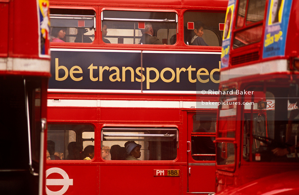 The slogan 'Be Transported' on the side of a red London double-decker Routemaster bus, urges Londoners to travel by public transport, rather than attempt to drive in the capital. Passengers on both the lower and upper decks of the bus operated by a number of bus companies such as Arriva.