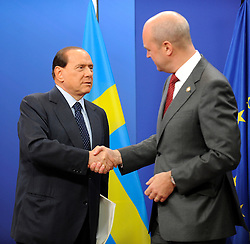 Silvio Berlusconi, Italy's prime minister, left, is greeted by Fredrik Reinfeldt, Sweden's prime minister and standing president of the European Council, as he arrives for the European Summit at the EU headquarters in Brussels, Belgium, on Thursday, Sept. 17, 2009. European Union leaders may call for sanctions on banks that pay excessive bonuses, fearing that runaway executive pay could trigger another financial crisis, a draft text showed. (Photo © Jock Fistick) *** Local Caption ***Silvio Berlusconi