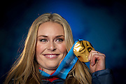Lindsey Vonn, USA, shows off her gold medal in the Women's Downhill at the 2010 Vancouver Winter Olympics in Whistler, British Columbia, Wednesday, Feb. 17, 2010.