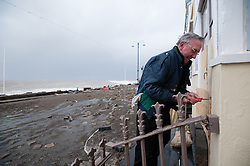 © Licensed to London News Pictures. 06/01/2014. Aberystwyth, UK. A resident battens Down his house in preparation. At either side of the high tide at 11.20am on Monday 06 Jan 2014, a deep depression drives a huge ground swell of waves to crash into the promenade at Aberystwyh, already partly destroyed by the storms of the past three days. Earlier Police and local authority officers had been going house to house on Aberystwyth promenade strongly advising ALL residents to evacuate their seafront properties immediately, in advance of these potentially very damaging set of high waves.  Photo credit : Keith Morris/LNP