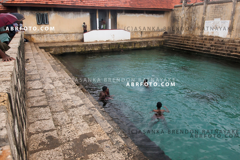 Men swimming in the a mineral water spring called Keerimalai Springs reputed for its curative properties