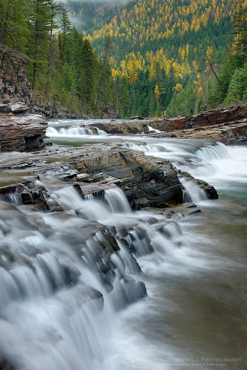 Waterfalls tumbling over layered sedimentary rocks of McDonald Creek, Glacier National Park Montana USA
