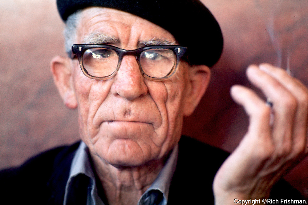 Photograph of older man, with weathered wrinkled face and thick dirty glasses, smoking in Caffé Trieste, a historic coffee house in San Francisco's North Beach neighborhood..©Rich Frishman.