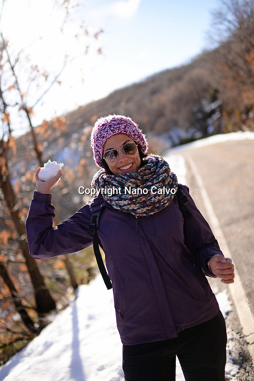 Young woman playing with snowballs in winter environment