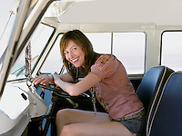 Young woman smiling in drivers seat of van