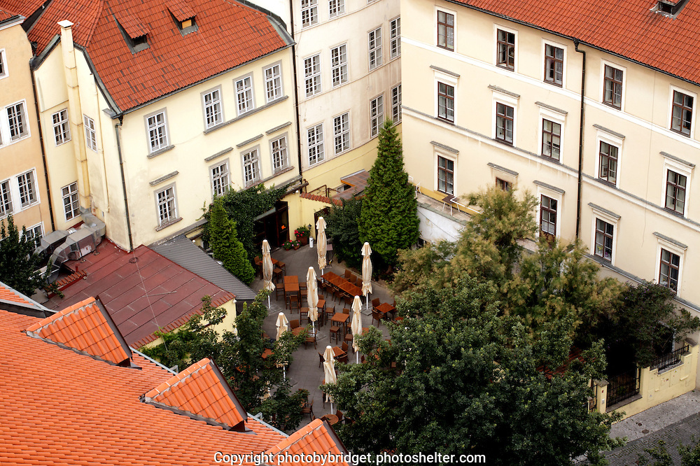 Editorial use only.<br /> <br /> A view from the Stare Mesto Tower in Prague over the city roofs, and gardens and restaurants. An outdoor summer restaurant with still folded umbrellas and surrounded by trees, around it building and red tile roofs.