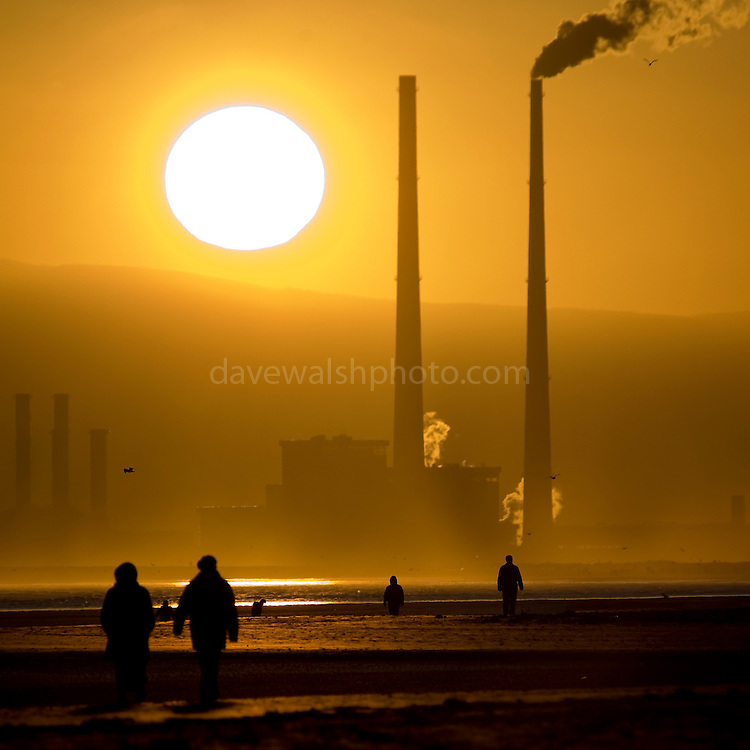 """Climate change: Source of solar energy setting behind user of fossil fuel energy - sun setting behind Poolbeg Generating station, Ringsend Dublin, The Walkers are on Bull Island, in North Dublin. The energy generating power station is Ireland's second most polluting installation in terms of carbon dioxide, co2 emissions, according to the European Environment Agency. <br /> <br /> This image was """"Highly Commended"""" in the """"Changing Climates"""" category at the 2009 Environmental Photographer of the Year competition."""