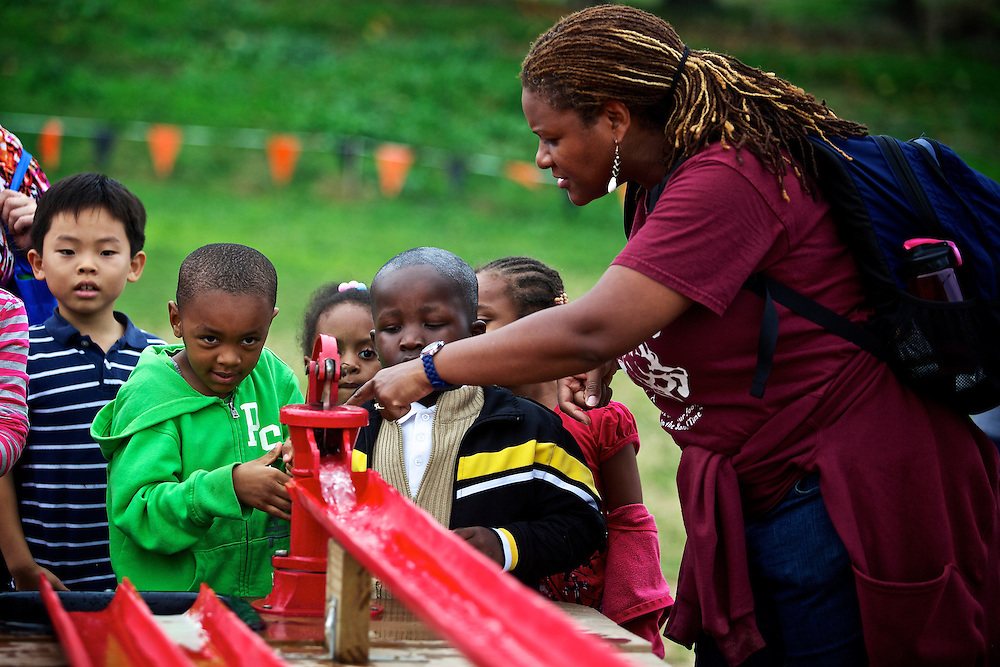 "Calvin Rodwell Elementary School Pre-kindergarten teacher Erika Parker, right, shows students, including Joshua Johnson-Bey, 4, left, how to use a water pump at Summers Farm in Frederick, MD on Oct. 24, 2012. The visit to the farm was part of a ""Common Core"" reading and learning unit for their class, which aims to follow up non-fiction reading with learning in the field. The day prior the children read a book about going to a farm."