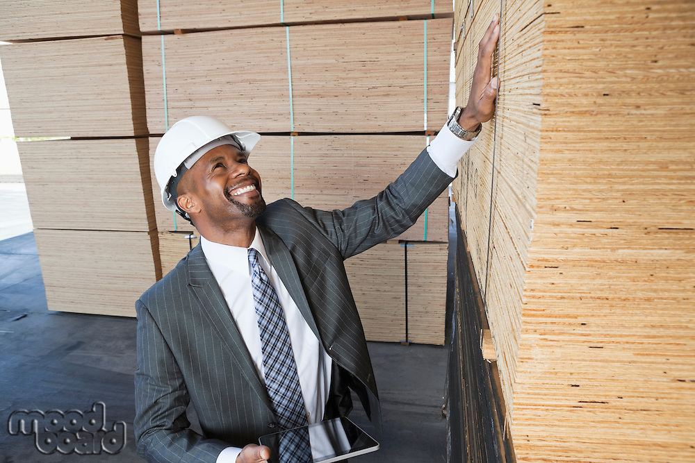 Happy African American male contractor inspecting wooden planks while holding tablet PC