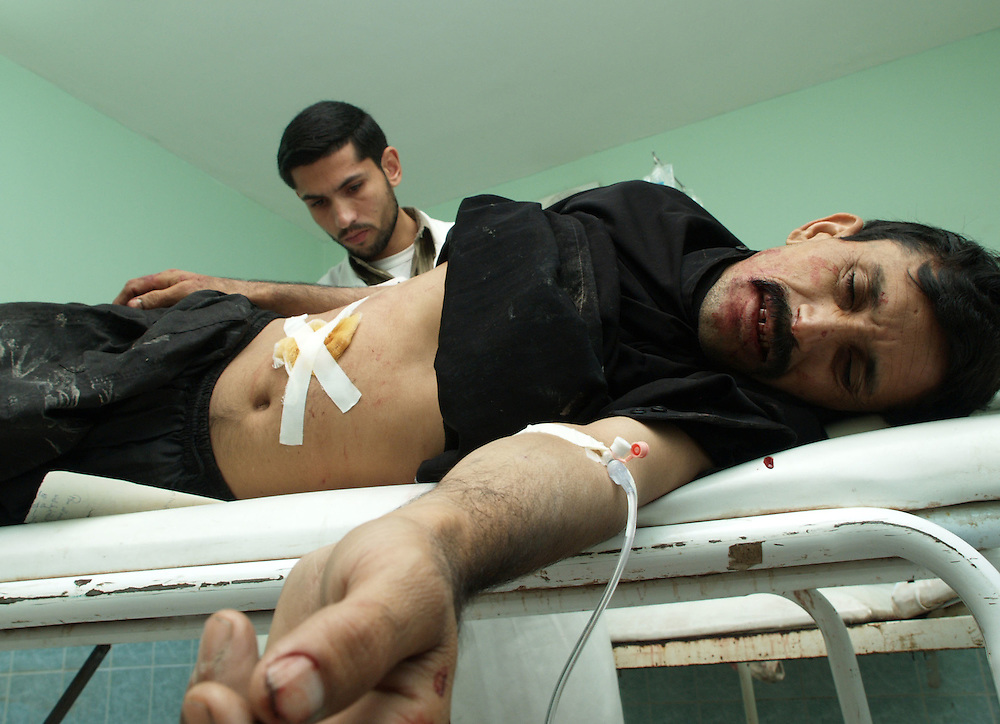13 January 2004.Basra, Iraq..Gun crime victims..Crime in Basra continues to take a heavy toll on inhabitants..Robbery and carjacking are frequently perpertrated at gunpoint..Many victims of crime are killed during the incidents, Basra's main hospital treats between 5 and 7 surviving gunshot victims each evening. .A local man writhes in pain during treatment for an injury caused by a bullet passing through his abdomen.