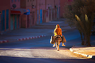 Man on donkey rides early morning on a road in Tinghir, Morocco.