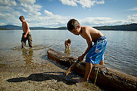 JEROME A. POLLOS/Press..Vincent Juarez, 12, plays along the shoreline of the beach at North Idaho College as his friends, James Ashline, 12, and Grace Ashline, 2, wade in the water Wednesday.