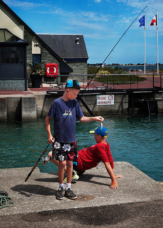 Boys fishing in the harbour in St. Vaast la Hougue, Normandy, France.<br />