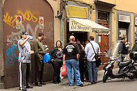 A group of tourists stand and  wait in line for a  great tasty  Florentine panino.