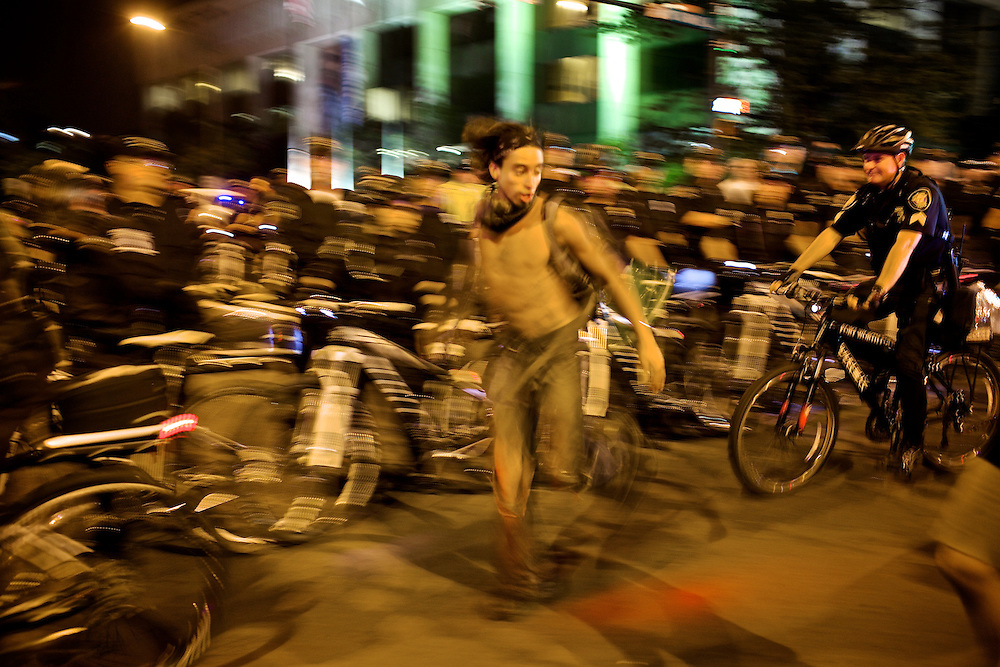 William Estrella, of the Occupy movement, dances around police that were blocking protestors from roadways in Charlotte, N.C. during the 2012 Democratic National Convention on Sept. 6, 2012.