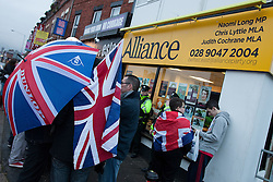 "© Licensed to London News Pictures . 11/01/2013 . Belfast , UK . Loyalist protesters stand in front of the office of the Alliance Party on the Newtownards Road in East Belfast today (11th January 2013) ahead of "" Operation Standstill "" . The protest is one of many that have been held since Belfast City Council voted to stop flying the Union flag above Belfast City Hall . Photo credit : Joel Goodman/LNP."