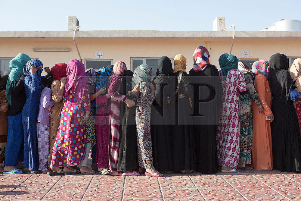 Licensed to London News Pictures. 22/10/2016. Female Iraqi IDPs, newly arrived from areas where the Mosul Offensive is taking place, queue for food served by aid workers in a school at the Dibaga refugee camp near Makhmur, Iraq. Upon arriving at the camp women and children stay in the school for around 10 - 15 days whilst completing the registration process.<br /> <br /> The crowded Dibaga camp, housing around 28,000 Sunni Arab refugees, is the main gathering point for new IDPs now fleeing areas where ISIS have been pushed out or are in conflict with the Iraqi Army. Photo credit: Matt Cetti-Roberts/LNP