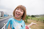 Konstnären Megumi Igarashi, som sedan fem år tillbaka går under pseudonymen Rokudenashiko pekar mot floden där hon paddlade sin kanot. Kanoten hade hon skrivit ut på en 3D skrivare i formen av hennes kön. Tokyo, Japan.