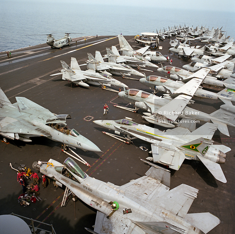 Up on the top deck of a US Navy aircraft carrier, parked F/A-18C Hornets and S-3 Vikings on the USS Harry S Truman during its deployment patrol of the no-fly zone at an unknown location in the Persian Gulf. Stacked together in tight formation to fit them all together during a daytime break in operations, the man bends into his task during the hottest time of day. The Truman is the largest and newest of the US Navy's fleet of new generation carriers, a 97,000 ton floating city with a crew of 5,137, 650 are women. The Iraqi no-fly zones (NFZs) were proclaimed by the United States, United Kingdom and France after the Gulf War of 1991 to protect humanitarian operations in northern Iraq and Shiite Muslims in the