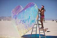 Koro Loko<br /> by: Emily Nicolosi<br /> from: Salt Lake City, UT<br /> year: 2019<br /> <br /> A billowing heart made of wire netting filled with hundreds of tiny dichroic plexi squares refracts the spectra of light in all directions. Benches under lightposts encircling the heart provide a place to hunker, commune and daydream. Like the exuberance of colors reflected by this heart, always-present and ever-shifting, this heart conjures the thousands of expressions and materializations of love prospected in the human experience.<br /> <br /> URL: https://sites.google.com/view/love-is-project/<br /> Contact: emily.nicolosi@gmail.com<br /> <br /> https://burningman.org/event/brc/2019-art-installations/?yyyy=&artType=B#a2I0V000001AW2sUAG
