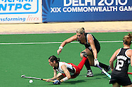 Dawn Mitchell of Wales falls as Clarissa Eshuis tackels during the pool B women's hockey match of the The Commonwealth Games between New Zealand and Wales held at the Stadium in New Delhi, India on the  October 2010..Photo by:  Ron Gaunt/SPORTZPICS/PHOTOSPORT